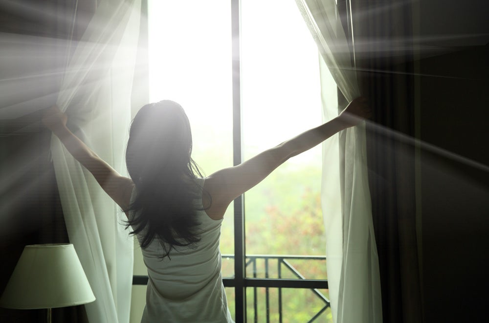 woman open curtains to sunshine